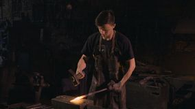 A young blacksmith is forging an iron