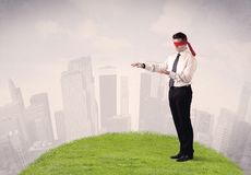 Blindfolded businessman with a cloudy city in the background Stock Photos