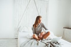 Young blogger or business woman working at home with social media, drinking coffee in early morning in bed Royalty Free Stock Image