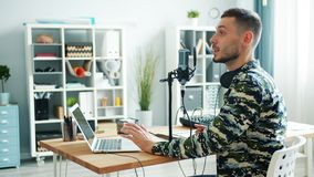 Young blogger using modern equipment to record podcast in home studio. Young blogger handsome bearded man is using modern equipment microphone sound mixer and stock video
