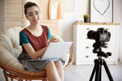 Young blogger with laptop in lounge chair recording video. At home Royalty Free Stock Photo
