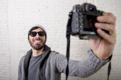 Young blogger man hipster style holding photo camera shooting selfie video and photo Royalty Free Stock Photo