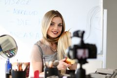 Young Blogger Recording Video Beauty Workshop. Caucasian Blond Girl Broadcast Haircare Vlog. Maquillage Master Styling Hair with Hairbrush by Camera royalty free stock images