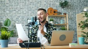Young blogger talking in microphone in studio reading from paper smiling. Young blogger attractive bearded man is talking in microphone in studio reading from stock video footage