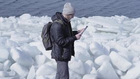 Young blond bearded handsome man in warm jacket and hat standing on the glacier checking with the map. Amazing nature of. Young blond bearded handsome man in stock footage