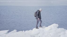 Young blond bearded handsome man wearing warm jacket, hat and boots climbing the glacier, walking on the edge. Amazing. Young blond bearded handsome man in a stock video footage