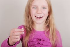 Young girl lost her first bottom front milk teeth. Childhood healthcare concept. Young blond beautiful girl lost her first bottom front milk teeth. Childhood stock photo