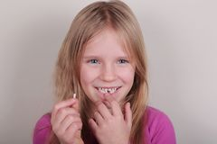 Young girl lost her first bottom front milk teeth. Childhood healthcare concept. Young blond beautiful girl lost her first bottom front milk teeth. Childhood royalty free stock photography
