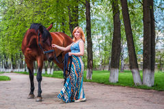 Young blond with a beautiful horse royalty free stock image