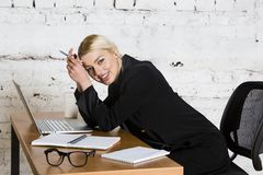 Young blond beauty businesswoman sitting at a office table with laptop, notebook and glasses in suit. Business concept. Stock Images