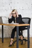 Young blond beauty businesswoman sitting at a office table with laptop, notebook and glasses in suit. Business concept. Young blond beauty businesswoman sitting royalty free stock photo