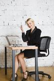 Young blond beauty businesswoman sitting at a office table with laptop, notebook and glasses in suit. Business concept. Young blond beauty businesswoman sitting royalty free stock photography