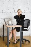 Young blond beauty businesswoman sitting at a office table with laptop, notebook and glasses in suit. Business concept. Royalty Free Stock Image