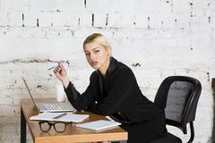 Young blond beauty businesswoman sitting at a office table with laptop, notebook and glasses in suit. Business concept. Stock Image