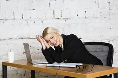 Young blond beauty businesswoman sitting at a office table with laptop, notebook and glasses in suit. Business concept. Young blond beauty businesswoman sitting stock images