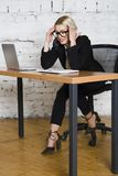 Young blond beauty businesswoman sitting at a office table with laptop, notebook and glasses in suit. Business concept. Young blond beauty businesswoman sitting stock photos