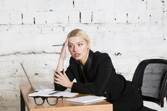 Young blond beauty businesswoman sitting at a office table with laptop, notebook and glasses in suit. Business concept. Young blond beauty businesswoman sitting stock image