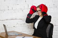 Young blond beauty businesswoman sitting at a office table with laptop, notebook and glasses in suit and boxing gloves. Stock Image