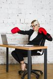 Young blond beauty businesswoman sitting at a office table with laptop, notebook and glasses in suit and boxing gloves. Young blond beauty businesswoman sitting stock image