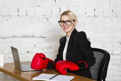 Young blond beauty businesswoman sitting at a office table with laptop, notebook and glasses in suit and boxing gloves. Young blond beauty businesswoman sitting stock photo