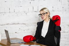 Young blond beauty businesswoman sitting at a office table with laptop, notebook and glasses in suit and boxing gloves. Young blond beauty businesswoman sitting stock images