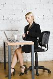 Young blond beauty businesswoman sitting at a office table with laptop, notebook and glasses in suit. Business concept. Royalty Free Stock Photos