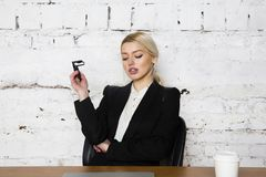 Young blond beauty businesswoman sitting at a office table with laptop, notebook and glasses in suit. Business concept. Royalty Free Stock Photography