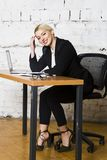 Young blond beauty businesswoman sitting at a office table with laptop, notebook and glasses in suit. Business concept. Stock Photo