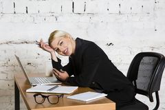Young blond beauty businesswoman sitting at a office table with laptop, notebook and glasses in suit. Business concept. Stock Photography