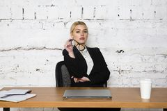 Young blond beauty businesswoman sitting at a office table with laptop, notebook and glasses in suit. Business concept. Young blond beauty businesswoman sitting stock photography