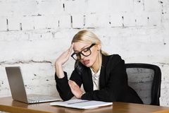 Young blond beauty businesswoman sitting at a office table with laptop, notebook and glasses in suit. Business concept. Young blond beauty businesswoman sitting royalty free stock image