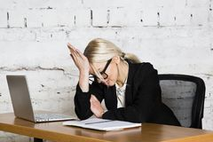 Young blond beauty businesswoman sitting at a office table with laptop, notebook and glasses in suit. Business concept. Young blond beauty businesswoman sitting royalty free stock photos