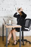 Young blond beauty businesswoman sitting at a office table with laptop, notebook and glasses in suit. Business concept. Young blond beauty businesswoman sitting royalty free stock images