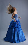 A young blond in a blue dress is shaking her hair Stock Image