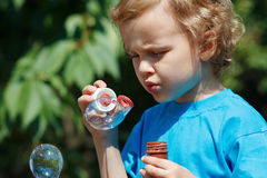 Young blond boy blowing a bubbles on a sunny day Stock Photography