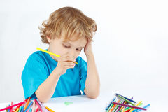 Young blond boy draws with color pencils Stock Photos
