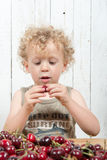 A young blond boy eating cherries Stock Images
