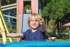 Young blond boy is playing at monkey bars. Stock Images