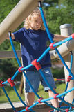 Young blond boy is playing at monkey bars. Royalty Free Stock Image