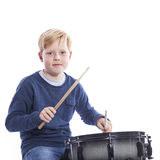 Young blond boy plays drum against white background Royalty Free Stock Image