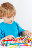 Young blond boy at the table with color pencils Royalty Free Stock Photos