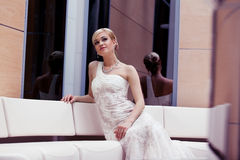 Young blond bride. With short hair in gown sitting in a hotel royalty free stock images