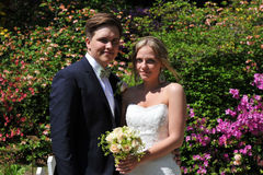 A Young blond Bride and a dark Groom. A Young Swedish couple with a blond Bride and a dark Groom in front of a haven of wonderful flowers, bougainvillea in May royalty free stock images