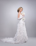 A young blond bride posing in a long white dress Royalty Free Stock Photos