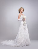 A young blond bride posing in a long white dress Royalty Free Stock Image
