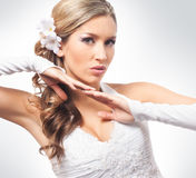 A young blond bride posing in a white dress Stock Images