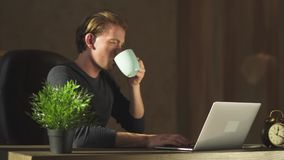 Thoughtful businessman working at notebook at the modern office drinking coffe. Young blond business man working at notebook in the modern office and drink tea stock video footage