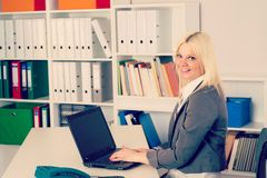 Young business woman in office. Young blond business woman in the office looking friendly in to the camera Stock Images