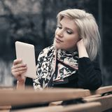 Young fashion blond business woman using tablet computer in city street Stock Photography