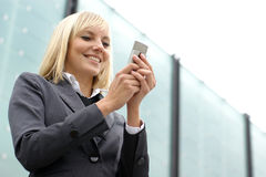 Young blond businesswoman is dialing the phone Royalty Free Stock Photography